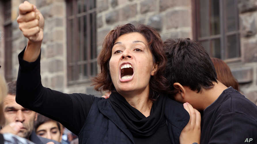 Emel Kitapci, the wife of Ali Kitapci, one of  the victims from Saturday's bomb attacks, reacts as she stands with her son Artun Siyah Kitapci, 11, during a demonstration at the site of the explosions,  in Ankara, Turkey, Oct. 12, 2015.