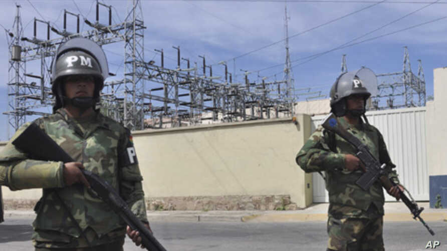 Military police stand guard outside Transportadora de Electricidad, the Spanish electricity grid's Bolivian subsidiary, in Cochabamba, Bolivia, Tuesday, May 1, 2012.