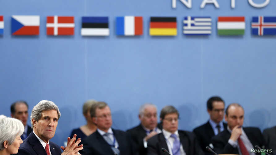 U.S. Secretary of State John Kerry (L) attends a NATO foreign ministers meeting in Brussels December 3, 2013.
