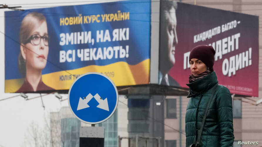 A woman stands in front of pre-election posters of opposition politician Yulia Tymoshenko and Ukrainian President Petro Poroshenko in Kyiv, Ukraine, Feb. 20, 2019.