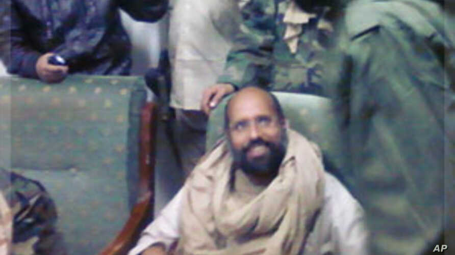 Saif al-Islam Gaddafi sitting with his captors in Obari airport November 19, 2011. Saif al-Islam has been captured in Libya's southern desert, scared and with only a handful of supporters