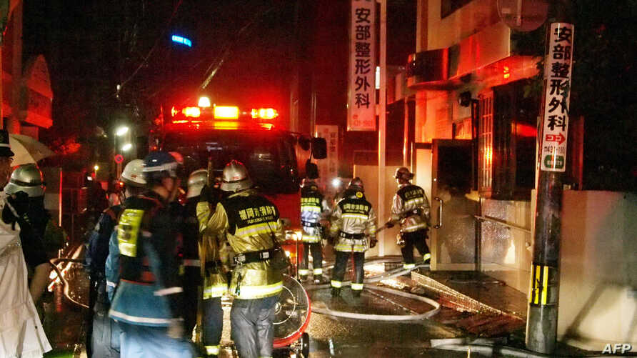 Firefighters attempt to contain a fire at a hospital in Fukuoka, western Japan on October 11, 2013. A fire broke out at a Japanese hospital early on October 11, killing 10 people, police said.  AFP PHOTO / JIJI PRESS    JAPAN OUT