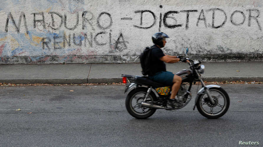 "FILE - A man on a motorcycle rides past a mural that reads, ""Maduro. Dictator. Resign"" during a blackout in Caracas, Venezuela, March 27, 2019."