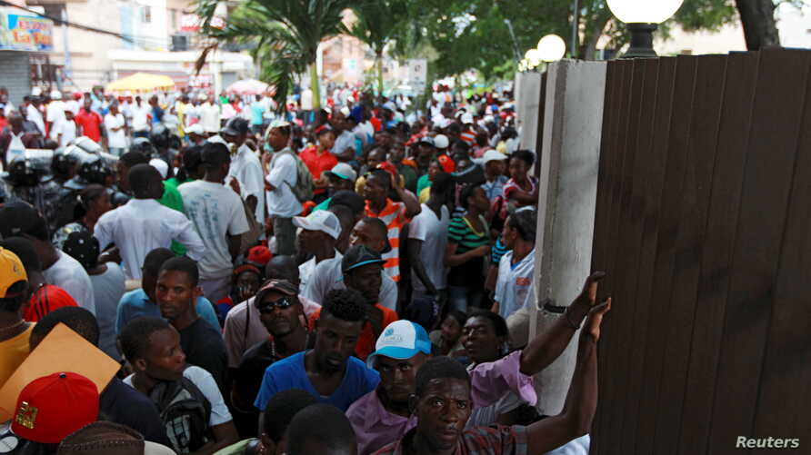 """Haitians stand outside the Ministry of Interior and Police while waiting to register in the so-called """"regularization"""" program, in Santo Domingo, June 17, 2015."""