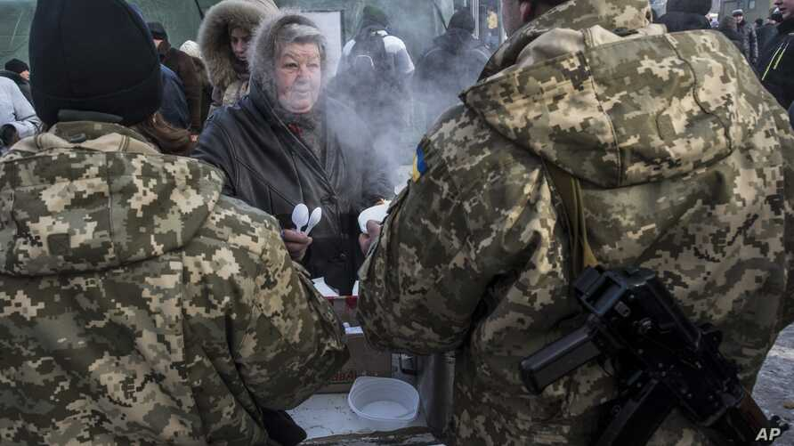 Ukrainian servicemen give out free food to local residents in Avdiivka, eastern Ukraine, Feb. 1, 2017.