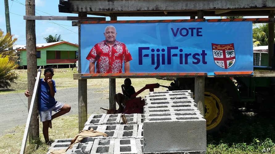 In this Nov. 7, 2018, photo, a FijiFirst poster with the image of Fiji Prime Minister Frank Bainimarama is displayed at the entrance to a village in Nausori, Fiji.