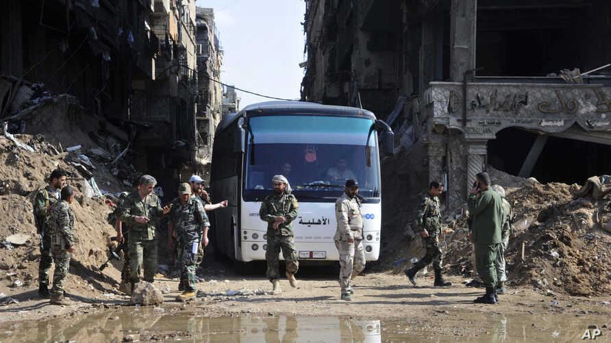 FILE - In this photo released on April 30, 2018 by the Syrian official news agency SANA, Syrian government forces gather in front of a bus carrying al-Qaida-linked fighters during an evacuation from the Palestinian refugee camp 0f Yarmouk, near Damas