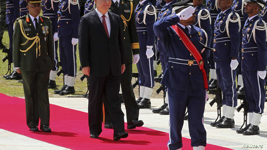 FILE - Chinese President Xi Jinping, second from left, inspects honor guards during an official welcoming ceremony in Male, Maldives, September 15, 2014.