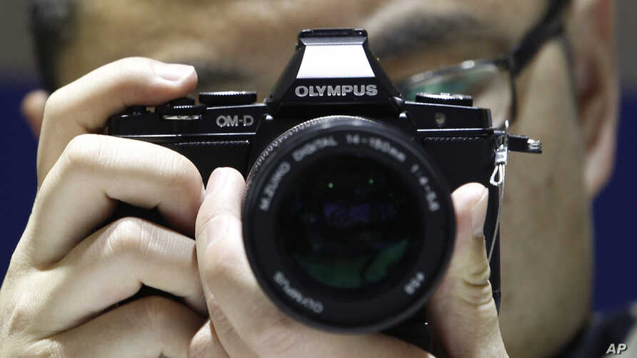 A Chinese visitor tries an Olympus digital camera, (File photo).