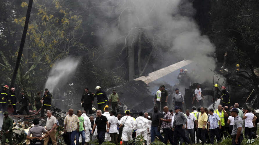 Cuba's President Miguel Diaz-Canel, third from left, walks away from the site where a Boeing 737 plummeted into a yuca field with more than 100 passengers on board, in Havana, Cuba, May 18, 2018. Cuban investigators have retrieved both black boxes fr