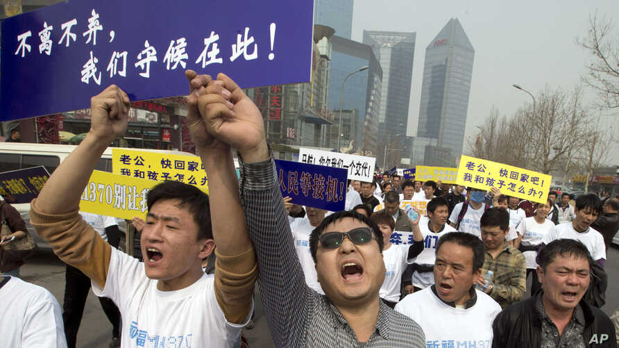 Chinese relatives of passengers onboard flight MH370 shout in protest as they march towards the Malaysia embassy in Beijing, March 25, 2014.