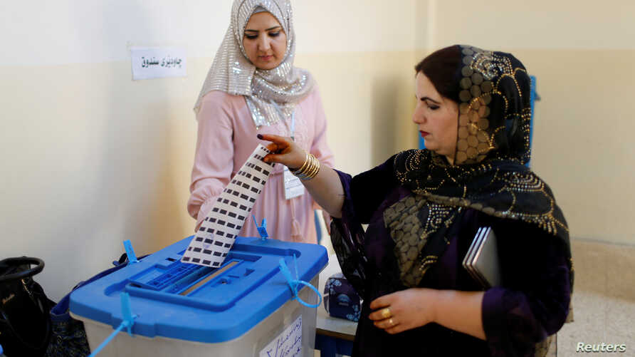 A Kurdish woman casts her vote at a polling station during parliamentary elections in the semi-autonomous region in Erbil, Iraq, Sept. 30, 2018.