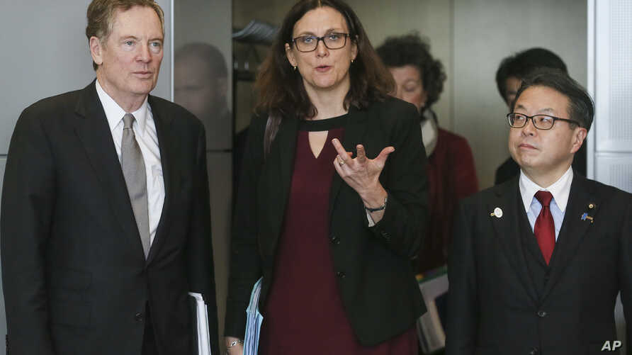FILE - European Commissioner for Trade Cecilia Malmstroem, center, Japanese Minister for Economy, Trade and Industry Hiroshige Seko, right, and U.S. Trade Representative Robert Lighthizer, pose for photographers prior to a meeting at EU headquarters