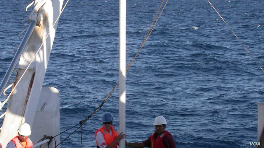 Scientists and sailors on the Indonesian research vessel, the RV Baruna Jaya VIII collect sediment cores off the coast of Indonesia. (Yair Rosenthal, Rutgers University)