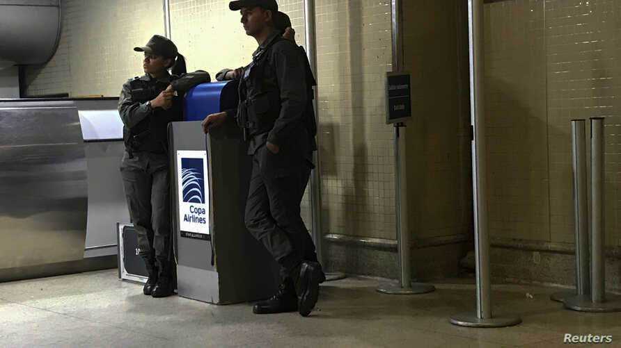 FILE - Venezuelan National Guards stand by a counter of Copa Airlines, at the Simon Bolivar airport in Caracas, Venezuela, April 6, 2018.