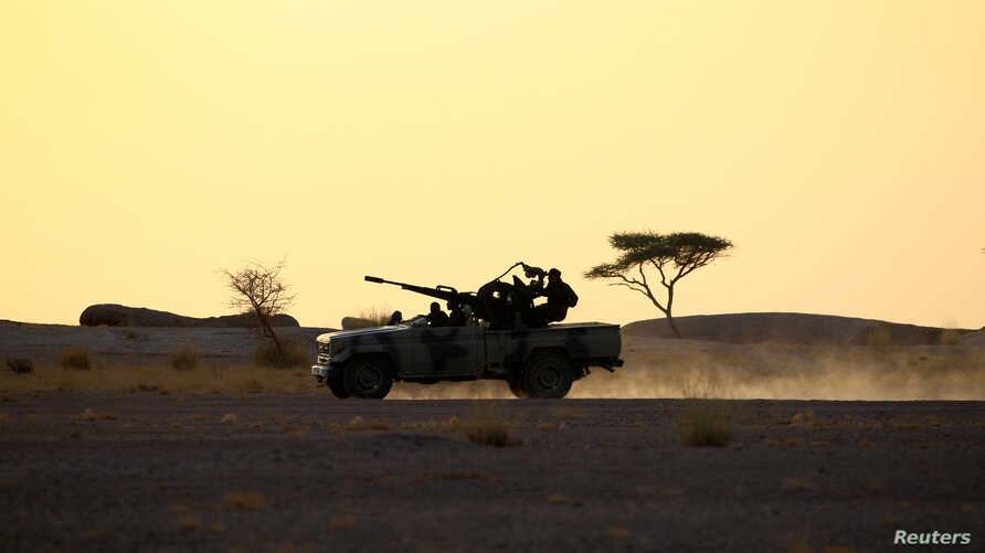 FILE - The Polisario Front soldiers drive a pick-up truck mounted with an anti-aircraft weapon at sunset in Bir Lahlou, Western Sahara, Sept 9, 2016.
