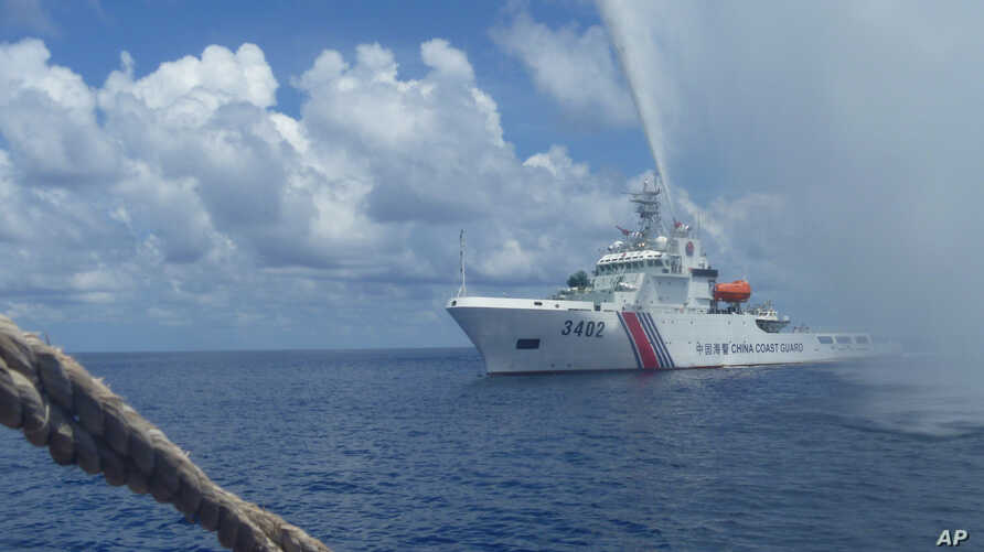 In this Sept.23, 2015 photo provided by Renato Etac, Chinese Coast Guard members approach Filipino fishermen as they confront them off Scarborough Shoal at South China Sea, in northwestern Philippines. (Renato Etac via AP)