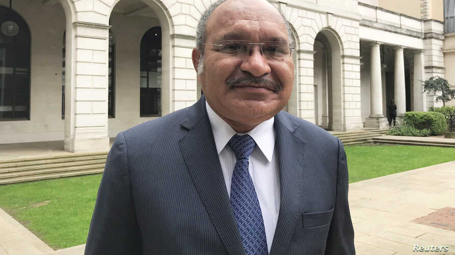 FILE - Papua New Guinea's Prime Minister Peter O'Neill stops for a photo as he attends an investment conference in London, Britain, April 24, 2018.