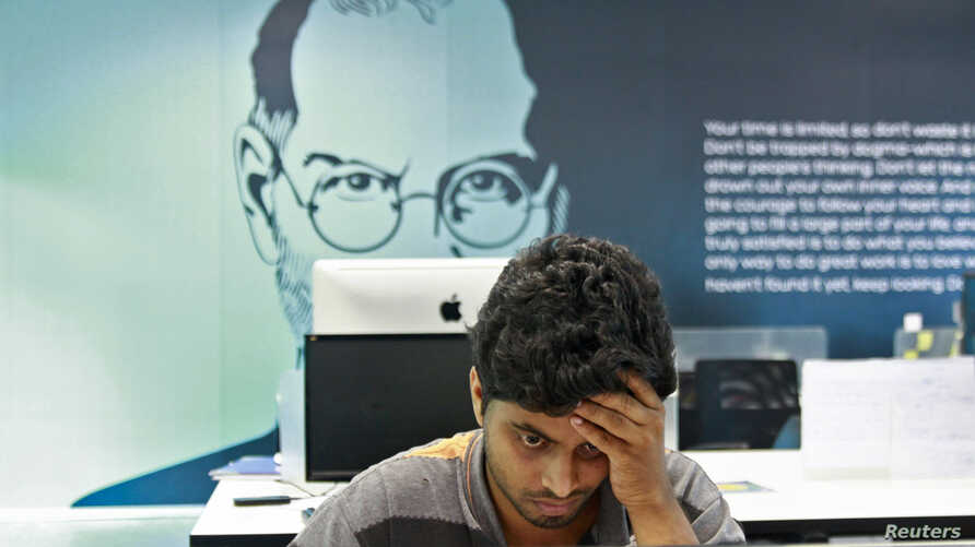 FILE - An employee works on a computer terminal against the backdrop of a picture of late Apple co-founder Steve Jobs at the Start-up Village in Kinfra High Tech Park in the southern Indian city of Kochi.