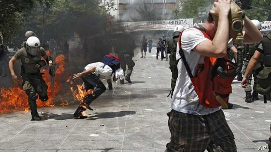 Riot police and demonstrators clash during protests against austerity measures in Athens, June 28, 2011.