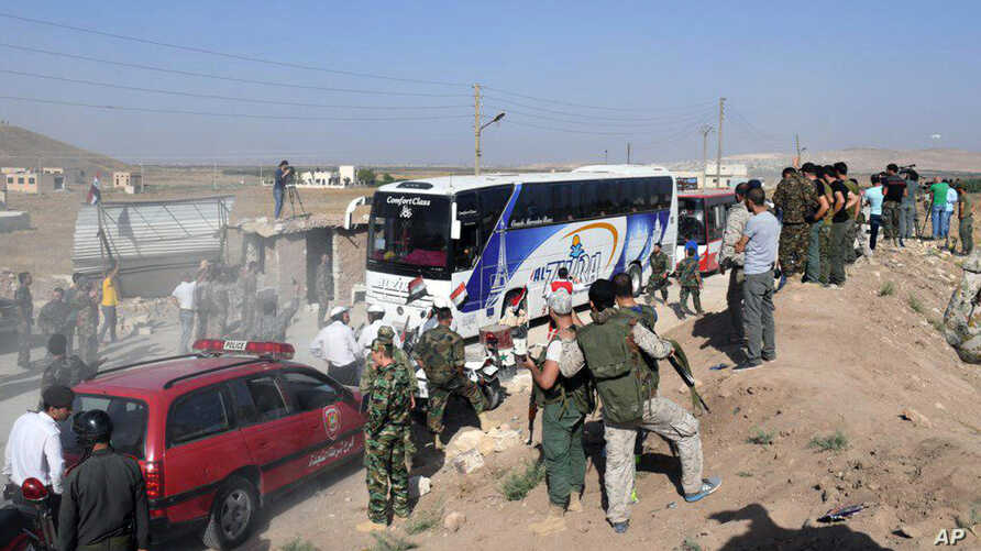 Photo released by the Syrian official news agency SANA shows Syrian troops, journalists, and civilians watching as buses evacuate people from the two pro-government villages of Foua and Kfarya, at Tel el-Eis, the crossing between Aleppo and Idlib pro