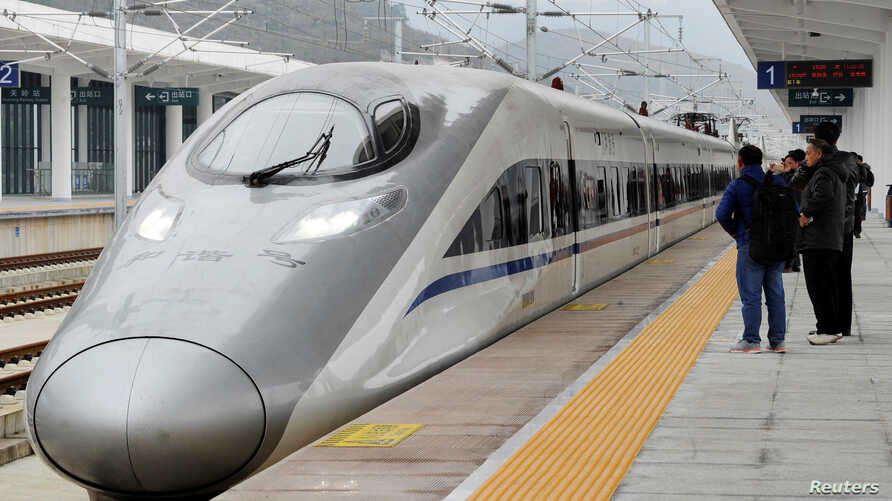 FILE - A high-speed railway train linking Shanghai and Kunming, of Yunnan province, is seen at a station during a partial operation, in Anshun, Guizhou province, China, Dec. 28, 2016.