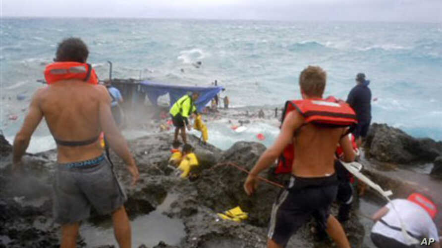 People clamber on the rocky shore on Christmas Island during a rescue attempt as a boat breaks up in the background. A wooden boat packed with dozens of asylum seekers smashed apart on cliff-side rocks in heavy seas off an Australian island Wednesday