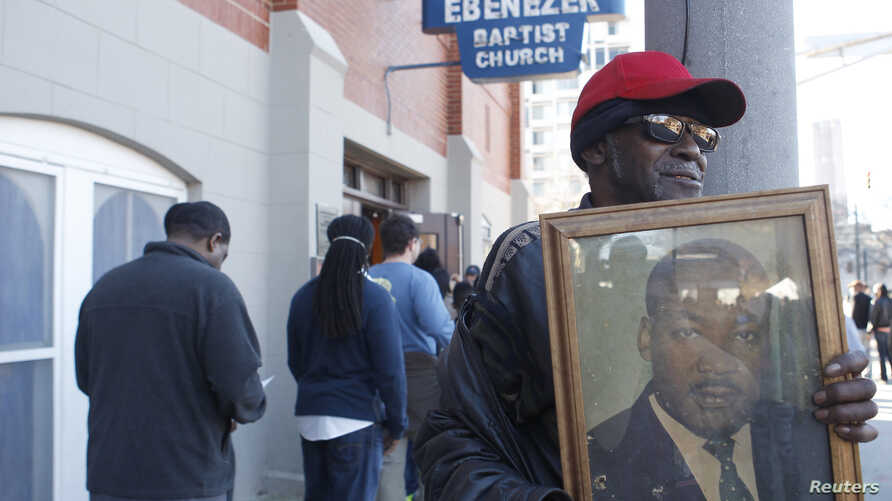 FILE - James Pender, Jr. stands in front of old Ebenezer Baptist Church where slain civil rights leader Martin Luther King, Jr. preached while holding a photograph of King, while visiting the King Center to commemorate the King Holiday in Atlanta, Ja