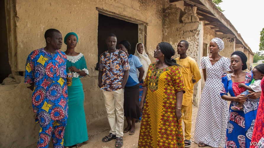 Rebecca Gadzama and schoolteachers survey the aging school building and discuss the upcoming school year.