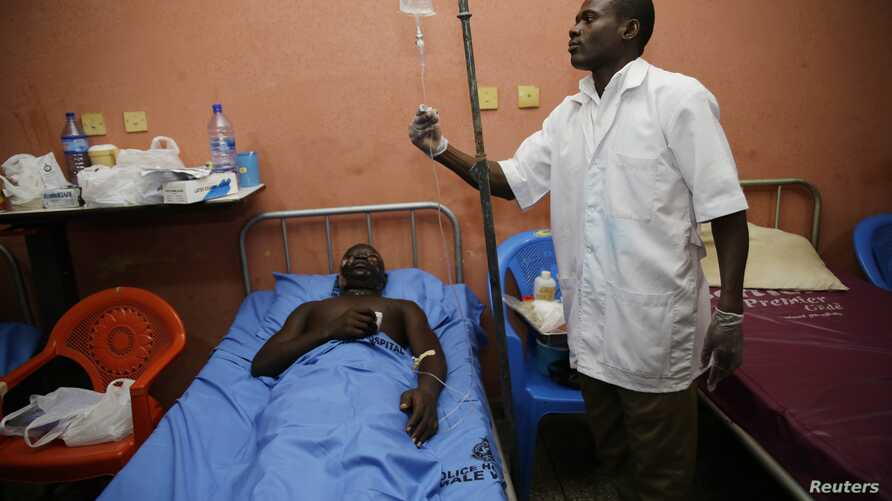 FILE - A doctor attends to a patient at a hospital in Accra, Ghana, June 5, 2015.