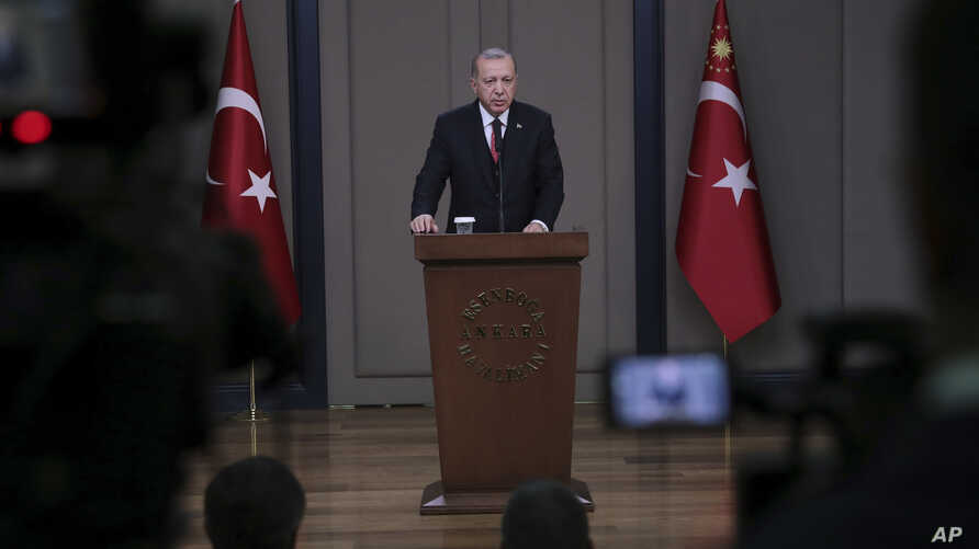 Turkey's President Recep Tayyip Erdogan talks to members of the media at the airport in Ankara, Turkey, before departing for a trip to France, Nov. 10, 2018.