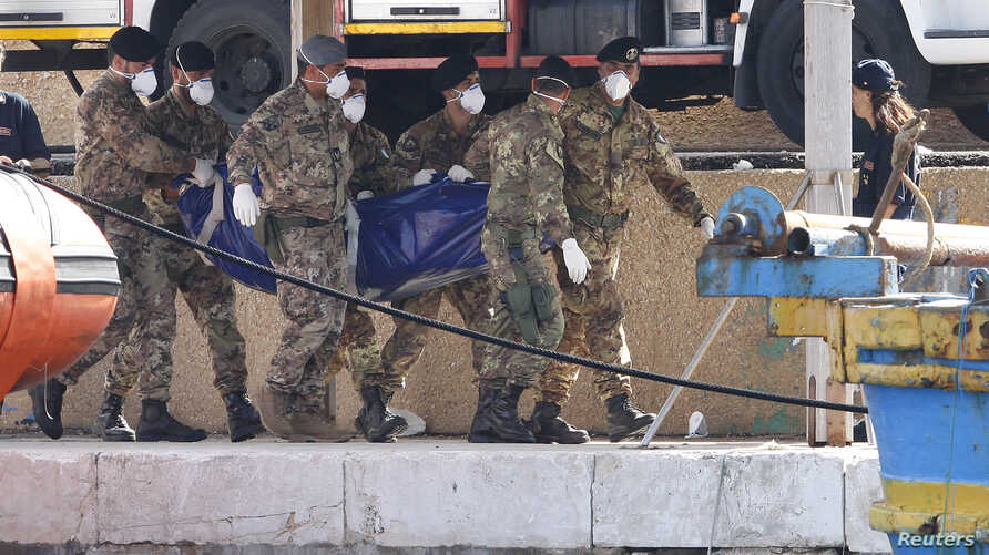 Soldiers carry the body of a victim of a shipwreck off Sicily in Lampedusa harbor October 6, 2013.