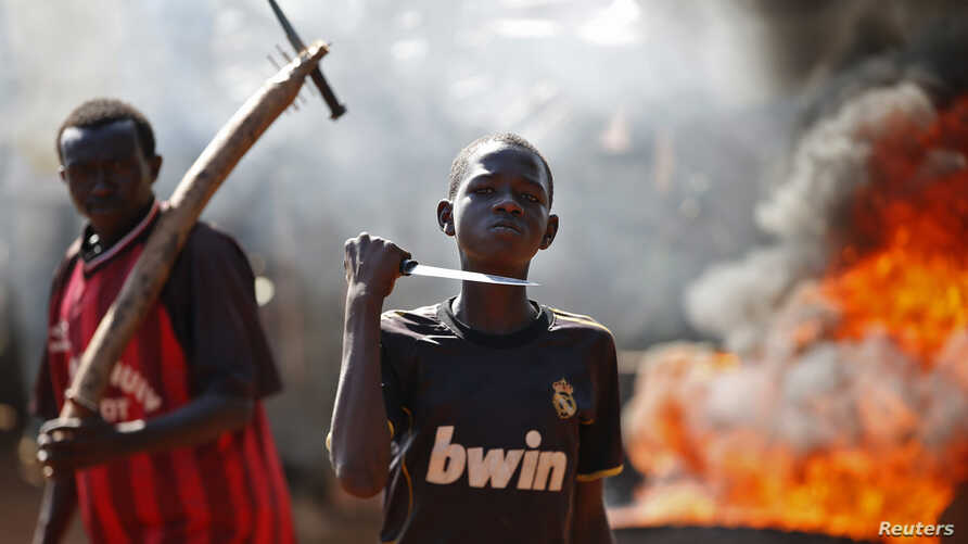 A boy gestures in front of a barricade on fire during a protest after French troops opened fire at protesters blocking a road in Bambari May 22, 2014.