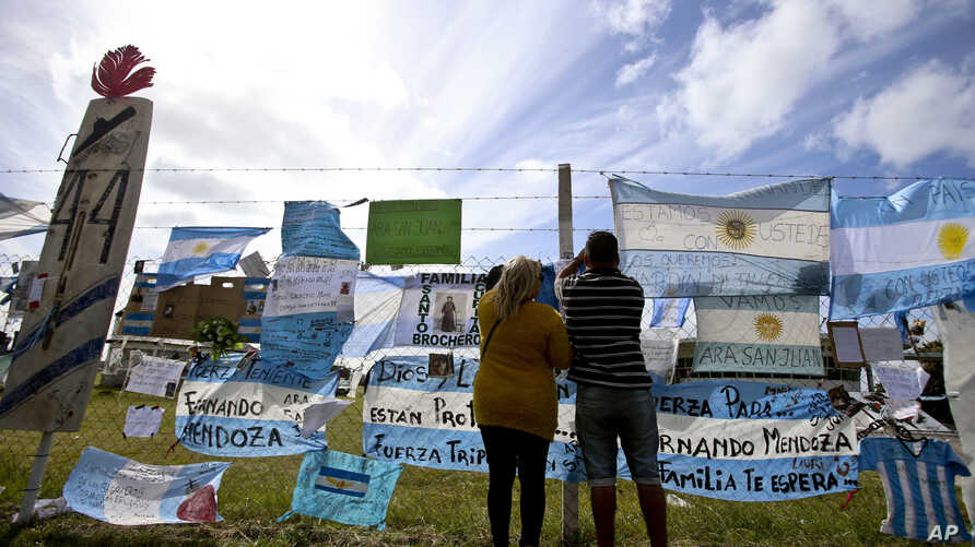 Friends and family of missing submarine crew members place a flag on the fence of the naval base in Mar de Plata, Argentina, Nov. 24, 2017.