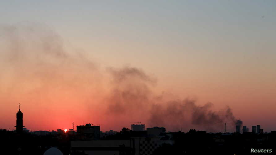 Black smoke billows in the sky above areas where clashes are taking place between pro-government forces, who are backed by the locals, and the Shura Council of Libyan Revolutionaries, an alliance of former anti-Gadhafi rebels, who have joined forces