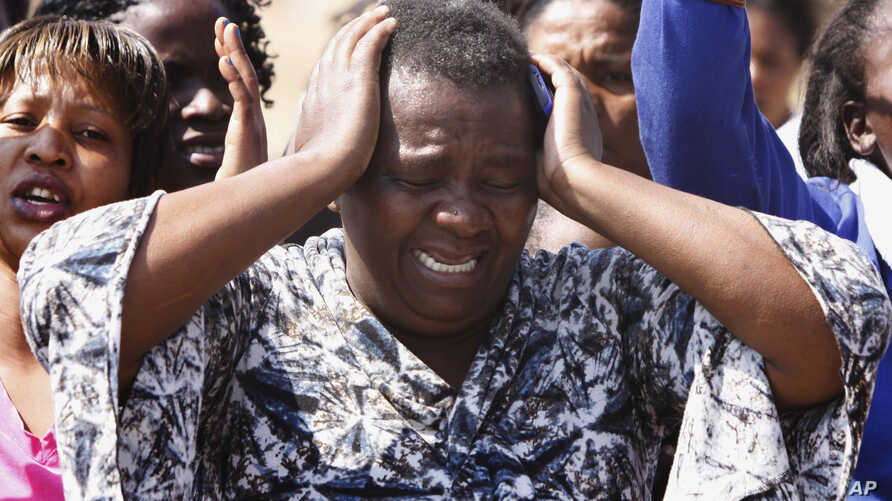 An unidentified woman cries as she protests against the police opening fire and killing striking mine workers a day earlier at the Lonmin Platinum Mine near Rustenburg, South Africa, August 17, 2012.