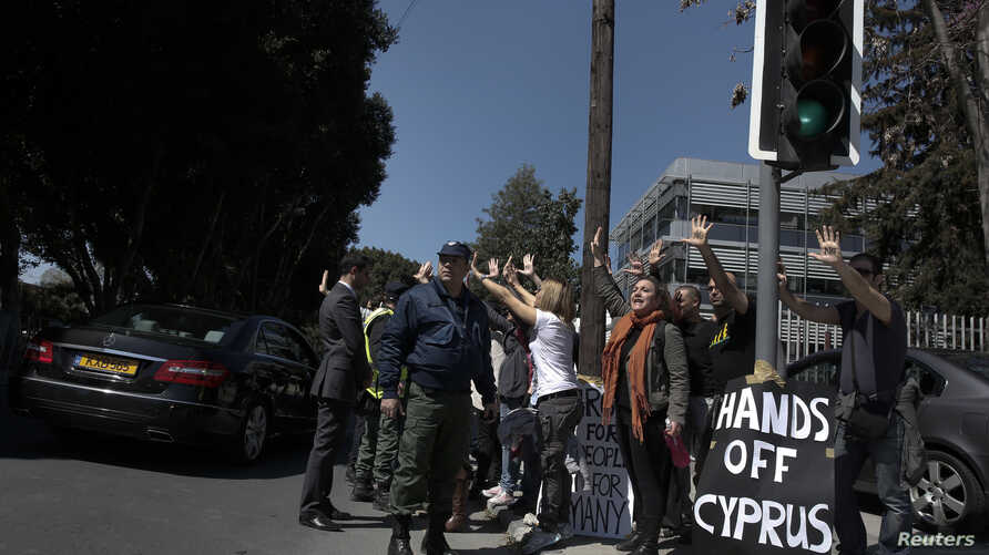 Demonstrators raise their arms in protest as Cypriot President Nicos Anastasiades's convoy drives to the parliament in Nicosia, Cyprus, March 18, 2013.