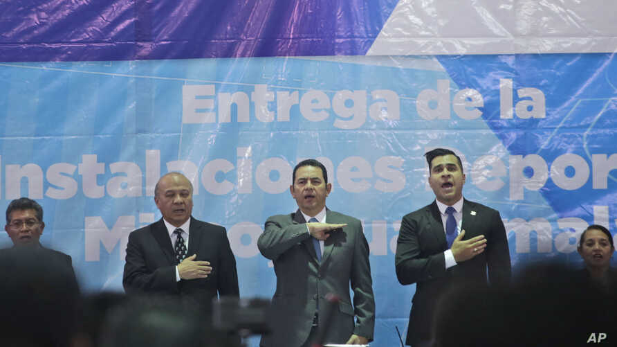 Guatemalan President Jimmy Morales, center, sings the national anthem, during the inauguration of a soccer field in Mixco, Guatemala, Sept. 17, 2018.