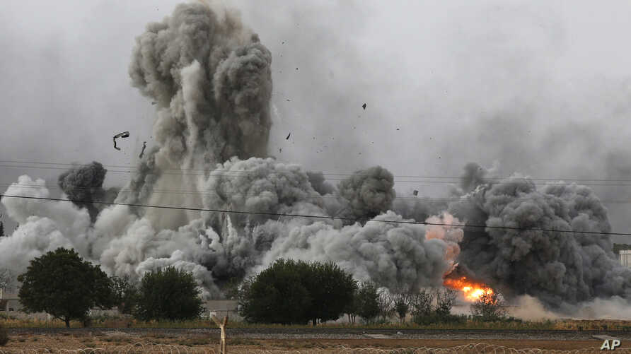 Thick smoke, debris and fire rise following an airstrike by the U.S.-led coalition in Kobani, Syria, as seen from Mursitpinar, on the outskirts of Suruc, at the Turkey-Syria border, Oct. 12, 2014.