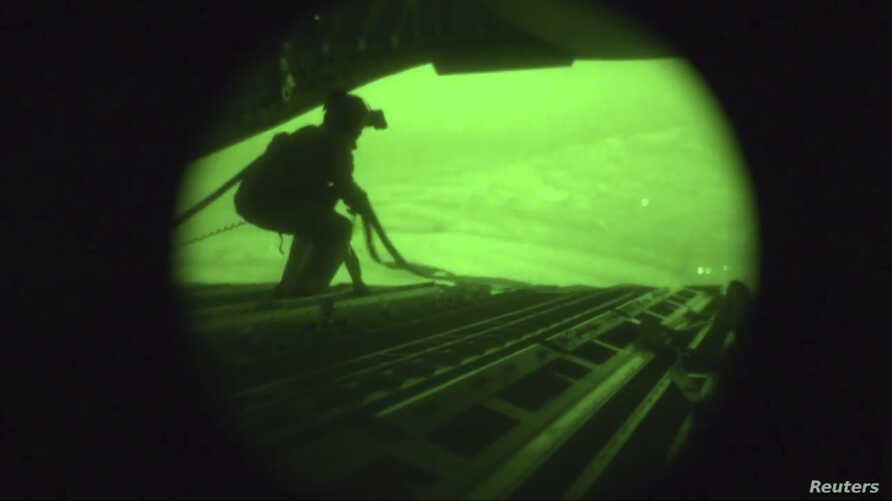 A still image captured from the U.S. Central Command night vision video footage shows an Air Force personnel retrieving straps after the U.S. military airdrop of food and water for thousands of Iraqi citizens threatened by the Islamic State of Iraq a