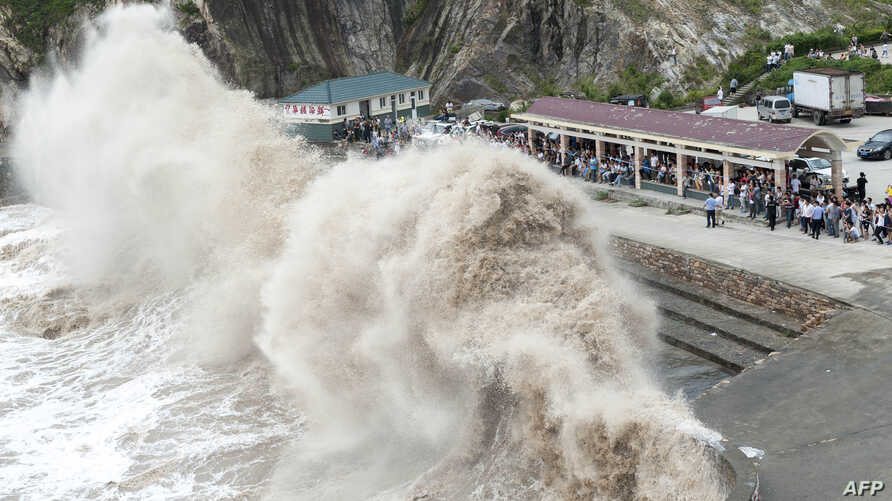 People gather to see huge waves as typhoon Chan-hom comes near Wenling, east China's Zhejiang province, July 10, 2015.