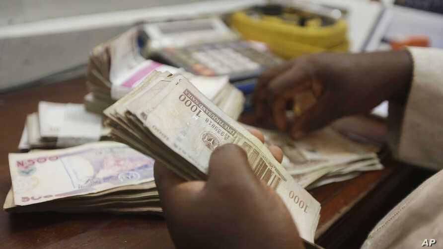 FILE - a money changer counts Nigerian naira currency at a bureau de change in Lagos, Nigeria, Oct. 20, 2015.