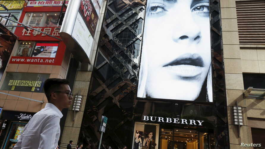 A model is seen on the screen of a Burberry store at Causeway Bay shopping district in Hong Kong, China, July 16, 2015