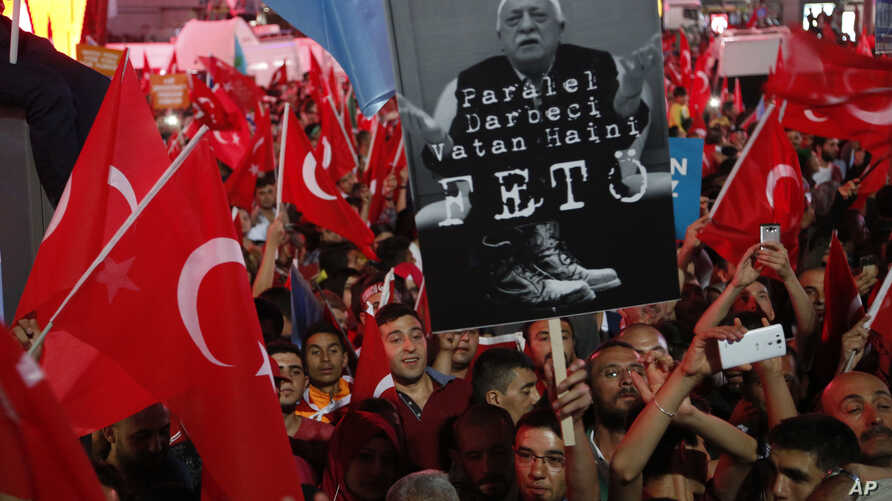 "Supporters of Turkish President Recep Tayyip Erdogan wave their national flags and hold a portrait of Fethullah Gulen, a U.S.-based Muslim cleric, with Turkish words that read: ""the Coup nation traitor, FETO"" (Feto is the nickname of Fethullah Gulen)..."