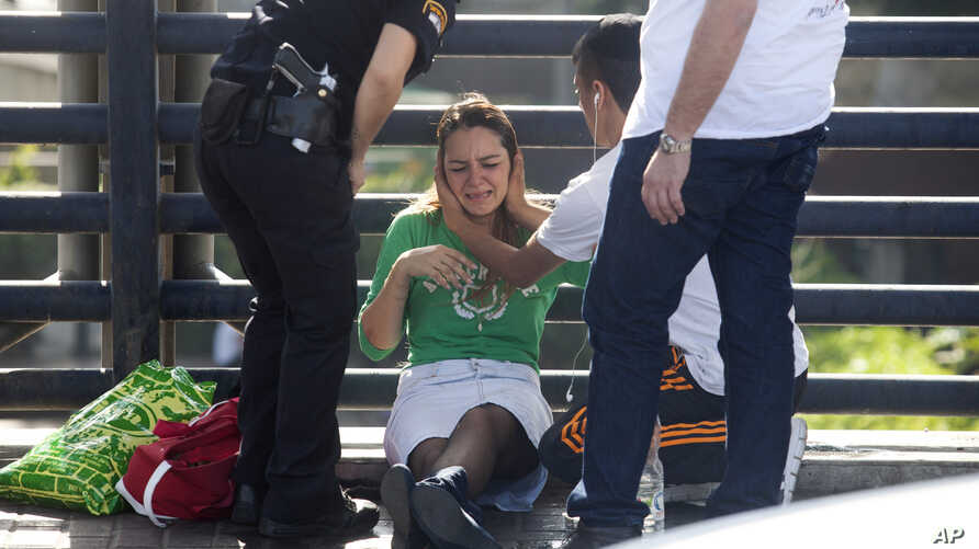 Paramedics treat a woman for shock after a soldier was stabbed in Tel Aviv, Israel, Nov. 10, 2014.