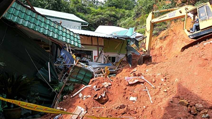 A rescuer uses a construction machine to search for the bodies believed to be buried by a landslide in Hulu Langat in central Selangor state, outside Kuala Lumpur, Malaysia, May 21, 2011.