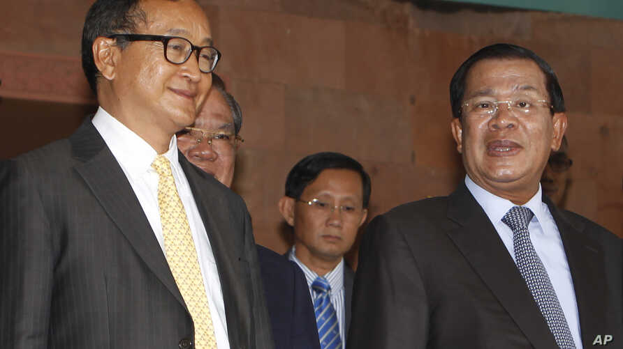 Cambodian Prime Minister Hun Sen, right, talks with the main Opposition Party leader Sam Rainsy, left, of Cambodia National Rescue Party, after their meeting in Senate headquarters in Phnom Penh, Cambodia, July 22, 2012.