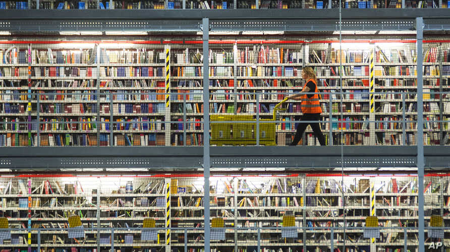 An employee works in the distribution center of the online retailer Amazon during a guided press tour prior to the upcoming Christmas business in Leipzig, central Germany, Thursday, Nov. 19, 2015.