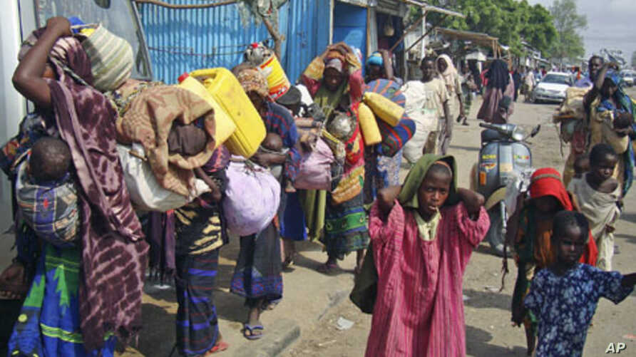 Internally displaced Somalis carry their belongings in search of greener pastures following a prolonged drought as they arrive in Somalia's capital, Mogadishu, July 4, 2011