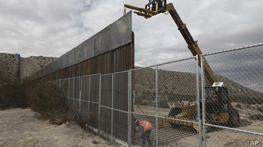 FILE - Workers raise a taller fence along the Mexico-US border between the towns of Anapra, Mexico and Sunland Park, New Mexico, Nov. 10, 2016. For almost two decades, a Mass has been celebrated there on the Day of the Dead to remember migrants who